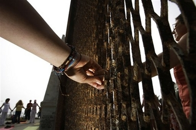 """Residents hold hands trough the U.S.-Mexico border fence as they take part in the """"Yoga without borders"""" encounter at the border in Tijuana, Mexico, Sunday, June 22, 2008.(AP Photo/Guillermo Arias)"""
